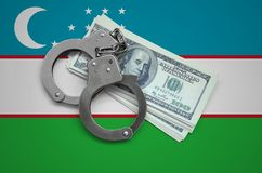 Uzbekistan flag with handcuffs and a bundle of dollars. Currency corruption in the country. Financial crimes.  stock images