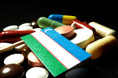 Uzbekistan flag with lot of medical pills isolated on black Royalty Free Stock Photo
