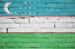 Uzbekistan flag is painted onto an old brick wall royalty free stock images