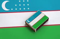 Uzbekistan flag is pictured on a matchbox that lies on a large flag.  royalty free stock images
