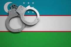 Uzbekistan flag and police handcuffs. The concept of crime and offenses in the country.  royalty free stock photos