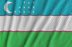 Uzbekistan flag printed on a polyester nylon sportswear mesh fab. Ric with some folds royalty free stock photos
