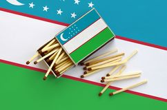 Uzbekistan flag is shown on an open matchbox, from which several matches fall and lies on a large flag.  stock images