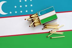 Uzbekistan flag is shown on an open matchbox, from which several matches fall and lies on a large flag.  royalty free stock photo