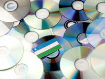 Uzbekistan flag on top of CD and DVD pile isolated on white. Uzbekistan flag on top of CD and DVD pile isolated Royalty Free Stock Photos