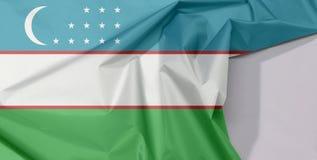 Uzbekistan tkaniny flaga zagniecenie z biel przestrzenią i krepa zdjęcia stock