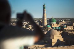 Uzbekistan. Tourist taking pictures on the roof of building in ancient city of Itchan Kala at sunny day, Khiva, Uzbekistan Royalty Free Stock Images