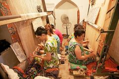 Uzbekistan. Uzbek women are working the silk carpet at the workshop in Itchan Kala, Khiva, Uzbekistan. Itchan Kala is the walled inner town of the city of Khiva Stock Photos