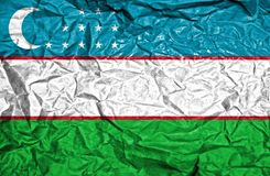 Uzbekistan vintage flag on old crumpled paper background stock photography