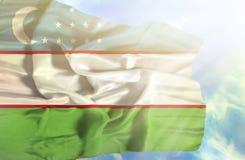 Uzbekistan waving flag against blue sky with sunrays stock photography