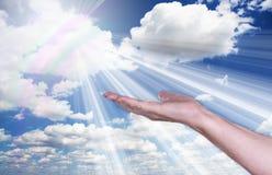 Uzdrawiać ręki w niebie z jaskrawym sunburst zdjęcia royalty free