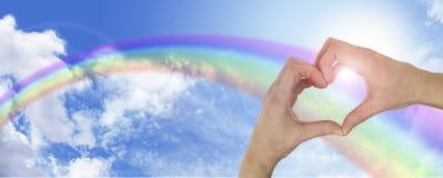 Uzdrawiać ręki na niebieskiego nieba i tęczy sztandarze Fotografia Royalty Free