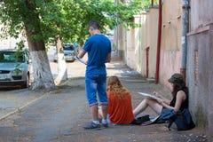 UZGHOROD - 23 DE JUNIO: tres trabajos de los pintores sobre la calle en Uzghor imagen de archivo libre de regalías