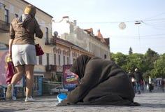 UZHGOROD,乌克兰- 2017年5月03日:可怜的老妇人乞求为施舍 免版税库存照片