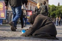 UZHGOROD UKRAINA - MAJ 03, 2017: Fattig tiggeri för gammal kvinna för allmosa Arkivbilder
