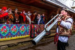 Eighth Ethnic Festival Christmas Carols in the old village. Uzhgorod, Ukraine - January 13, 2018: Member of folklore band plays on trembita during the eighth stock photography