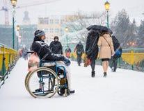 UZHGOROD,UKRAINE - JANUARY 04, 2017: Poor man in wheelchair begging for alms in the street. Of Uzhhorod, Ukraine stock images