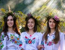 Portraits of three Young ladies with wreath. Uzhgorod, Ukraine - 07 Jul, 2016: Portraits of three Young ladies with traditional wreath on their heads. background Royalty Free Stock Images