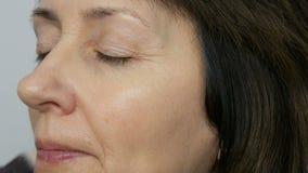 Uzupełnia artysty robić makeup z highlighter concealer w średnim wieku kobieta z niebieskimi oczami Pełnoletni makeup Zakończenie zdjęcie wideo