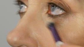 Uzupełnia artysty robić makeup z highlighter concealer w średnim wieku kobieta z niebieskimi oczami Pełnoletni makeup Zakończenie zbiory