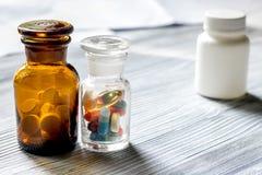 uzupełnia witaminy Pigułki i pigułki butelka na popielatym drewnianym stołowym tła copyspace Fotografia Stock