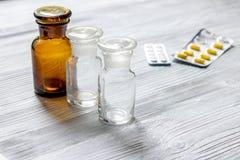 uzupełnia witaminy Pigułki i pigułki butelka na popielatym drewnianym stołowym tle Zdjęcie Stock