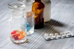 uzupełnia witaminy Pigułki i pigułki butelka na popielatym drewnianym stołowym tle Zdjęcia Stock