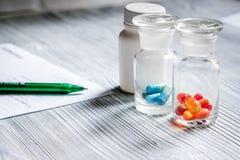 uzupełnia witaminy Pigułki i pigułki butelka na popielatym drewnianym stołowym tle Zdjęcie Royalty Free