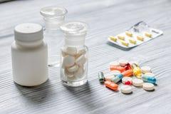 uzupełnia witaminy Pigułki i pigułki butelka na popielatym drewnianym stołowym tle Fotografia Stock