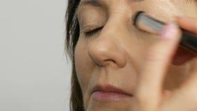 Uzupe?nia artysty robi? makeup z highlighter concealer w ?rednim wieku kobieta z niebieskimi oczami Pe?noletni makeup Zako?czenie zbiory wideo