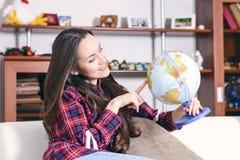 Vá em uma aventura Mulher que sonha sobre a viagem em todo o mundo, olhando o globo na sala da casa Estudo bonito da menina imagem de stock royalty free