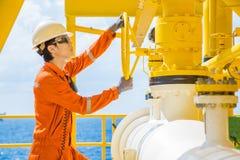 Válvula aberta do operador da produção para permitir o gás que flui à linha tubulação do mar para o gás e o óleo bruto enviados à fotografia de stock