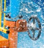 Válvula azul de la rueda con el tubo y wather que inunda alrededor en verano Imagen de archivo libre de regalías