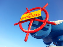 A válvula com um sinal de aviso no fundo do céu azul Fotografia de Stock