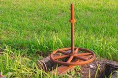Válvula da água e oxidado velhos na grama imagens de stock