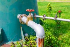 A válvula da água velha e a tubulação de aço comum da torneira do encanamento com fim vermelho do botão acima com espaço da cópia fotos de stock royalty free