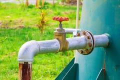 A válvula da água velha e a tubulação de aço comum da torneira do encanamento com fim vermelho do botão acima com espaço da cópia imagens de stock