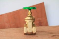 Válvula de bronze com botão verde em um encanador da fábrica no floo de madeira imagem de stock