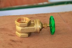 Válvula de bronze com botão verde em um encanador da fábrica no floo de madeira foto de stock royalty free