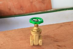 Válvula de bronze com botão verde em um encanador da fábrica no floo de madeira imagens de stock royalty free