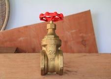 válvula de bronze com botão vermelho em um encanador da fábrica no assoalho de madeira imagens de stock