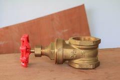 Válvula de bronze com botão vermelho em um encanador da fábrica no fundo de madeira do assoalho fotos de stock royalty free
