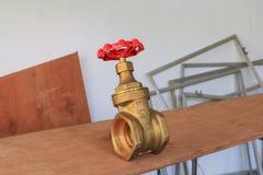 Válvula de bronze com botão vermelho em um encanador da fábrica no fundo de madeira do assoalho imagem de stock