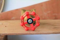 Válvula de bronze com botão vermelho em um encanador da fábrica no fundo de madeira do assoalho imagens de stock
