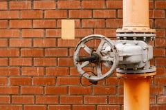 Válvula de gas en el tubo industrial de la distribución amarilla del gas natural delante de la pared de ladrillo roja con el copy Imagenes de archivo