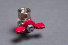 Válvula del agua con la manija roja en gris Fotografía de archivo libre de regalías