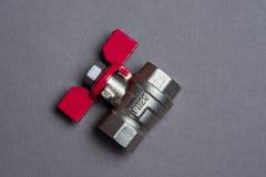 Válvula del agua con la manija roja en gris Fotos de archivo