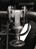 Válvula industrial do grande metal velho com o punho redondo montado em uma grande máquina preta com parafusos e as tubulaçõe imagem de stock