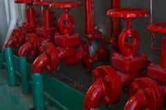 Válvula roja en el tubo verde Válvula con la manija de la rueda Engranaje industrial Fotos de archivo