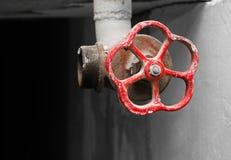 Válvula roja para el abastecimiento de agua en el sótano oscuro Imagenes de archivo